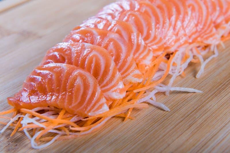 在木板背景的新鲜的三文鱼生鱼片 日本食物 库存图片