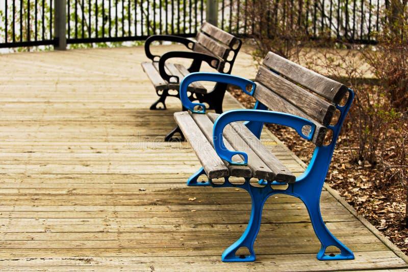 在木板走道的两条五颜六色的长凳 库存照片
