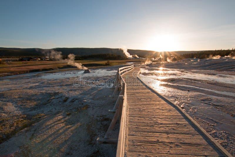 在木板走道的日落老忠实的喷泉水池的在黄石国家公园在怀俄明美国 免版税图库摄影