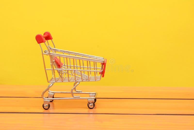 在木板backgorund的空的使用的购物的台车照片 库存照片