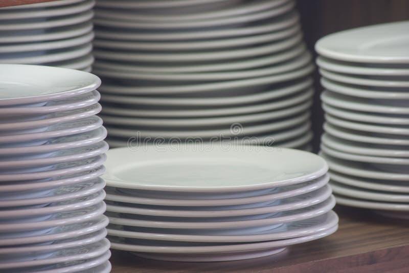 在木架子安置的堆白色干净的盘为自助餐做准备早晨 软绵绵地集中 免版税库存图片