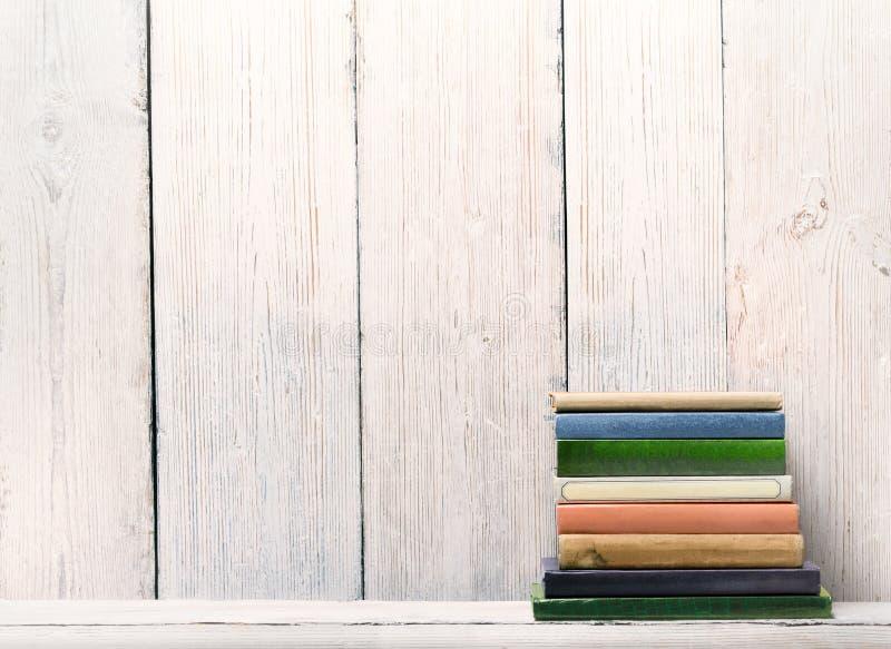 在木架子,在白色木墙壁的脊椎盖子的旧书 免版税库存照片
