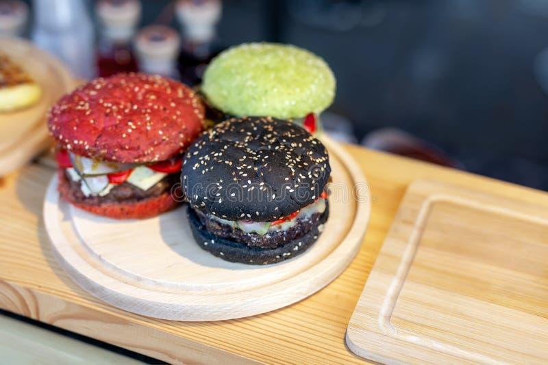 在木柜台的三个鲜美明亮的多彩多姿的牛肉汉堡在食物费斯特amburger小圆面包clolred用蕃茄,蓬蒿和 免版税库存图片