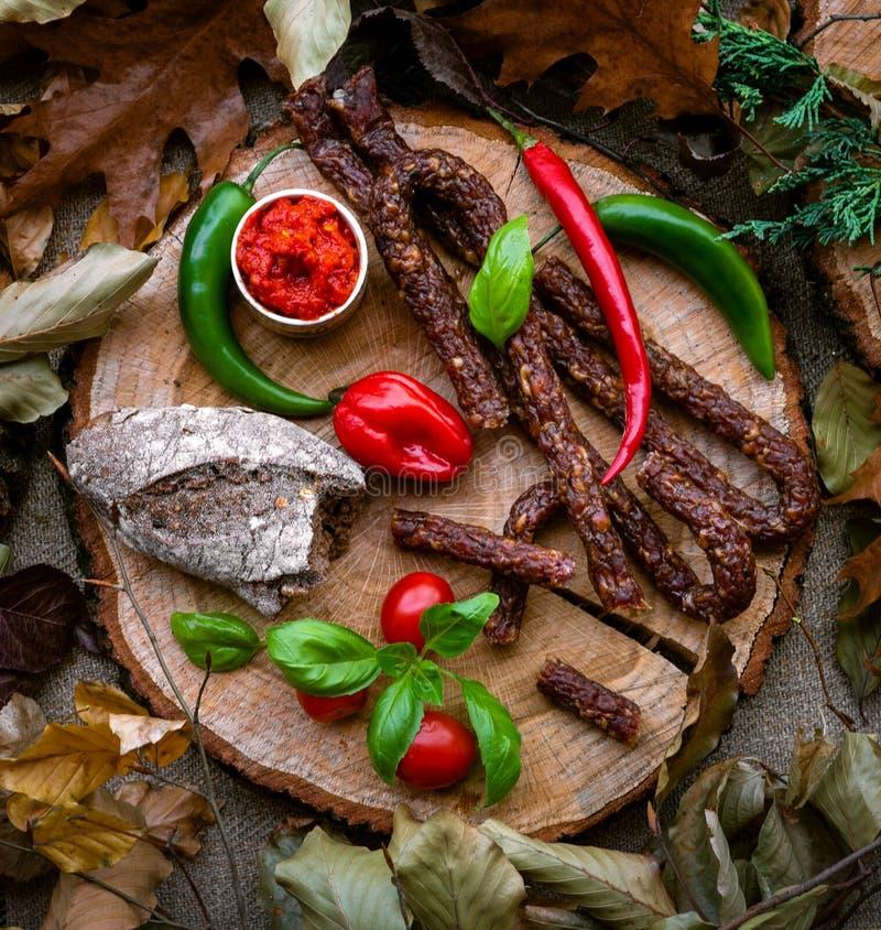 在木树干的快餐棍子熏制的香肠 免版税库存图片