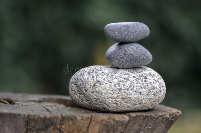 在木树桩,白色和灰色凝思小卵石的三块禅宗石头堆耸立 免版税库存照片