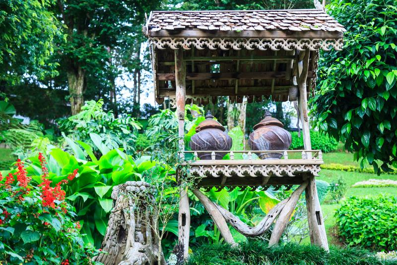 在木树荫风雨棚下的传统饮用水陶器容器在自然公园ba的绿色热带装饰庭院里 库存图片