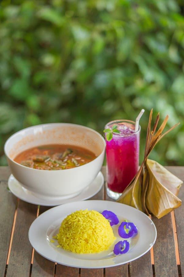 在木桌、姜黄米,金合欢事假煎蛋卷和虾上的传统泰国食物在辣酸汤留下蝴蝶豌豆汁 库存照片