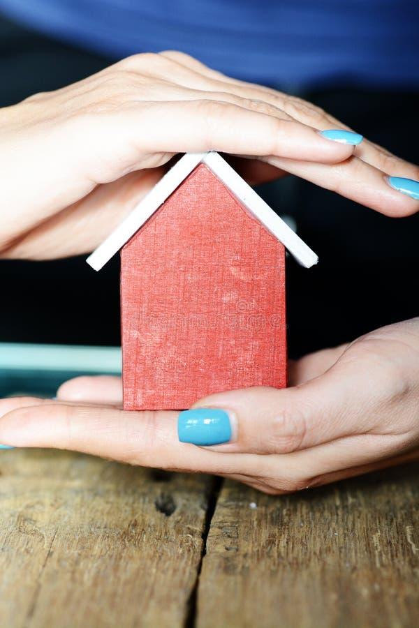 在木桌、房子或者家庭保险概念的妇女手的保护的五颜六色的玩具房子 库存图片