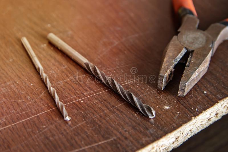 在木桌、钳子和钻子上的仪器有光的 库存照片
