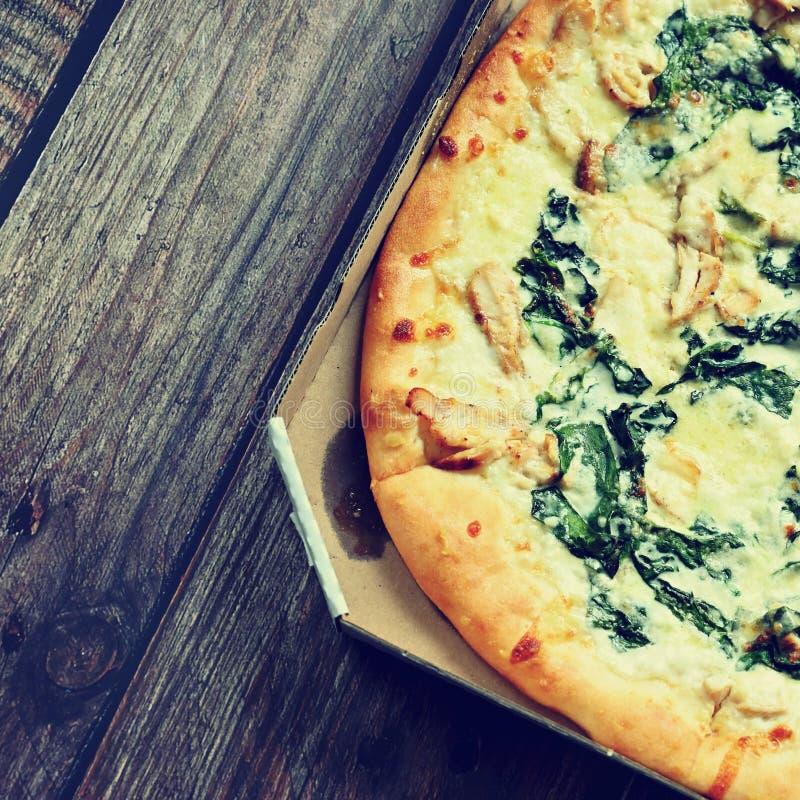 在木桌上供食的可口新鲜的比萨 与奶油和菠菜的比萨准备好在箱子的交付 库存照片