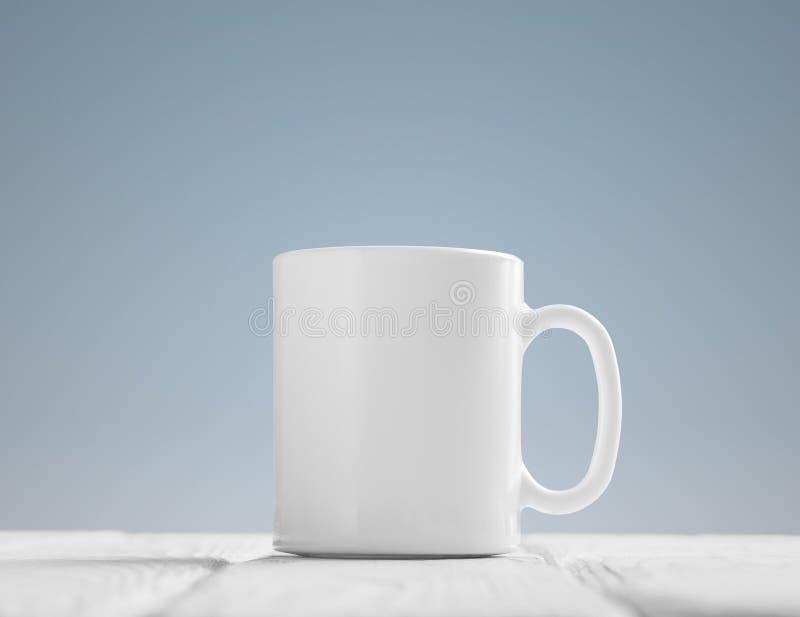 在木桌上倾斜的白色杯子大模型