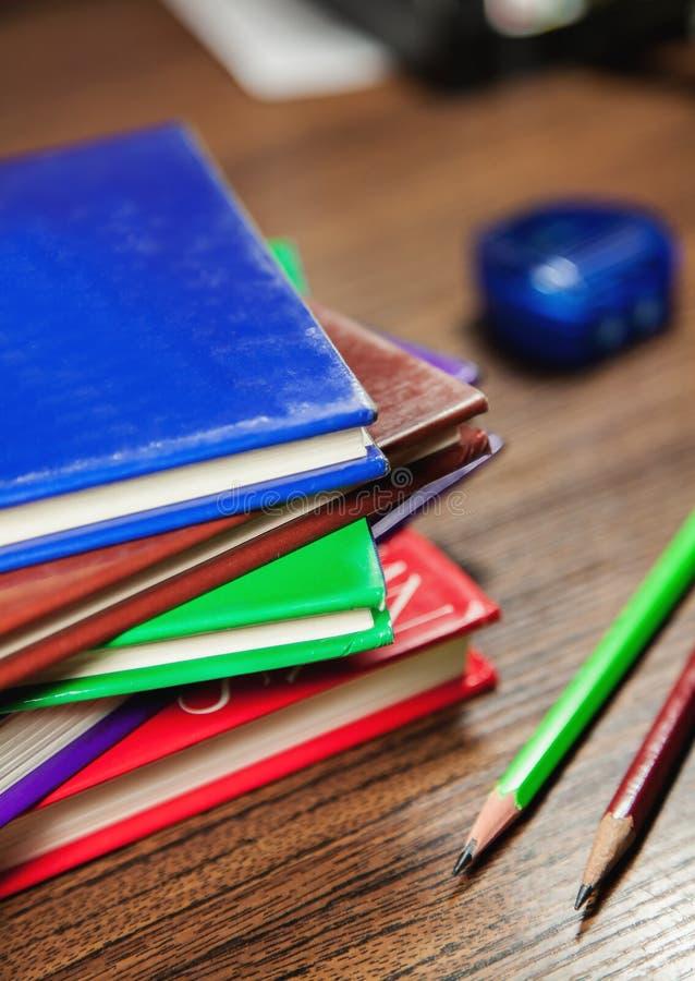 在木桌上堆积的色的书 免版税库存图片