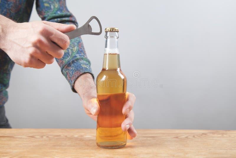 在木桌上开瓶啤酒的人 免版税图库摄影