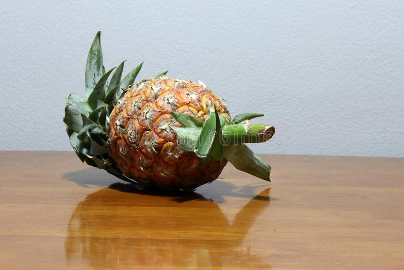 在木桌上把放的菠萝 E 库存图片