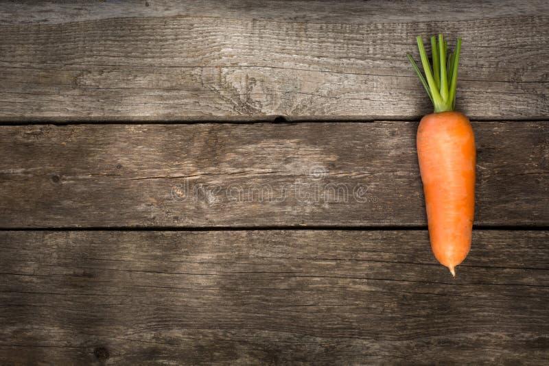 在木桌上的一棵新鲜的有机红萝卜 复制空间 库存照片