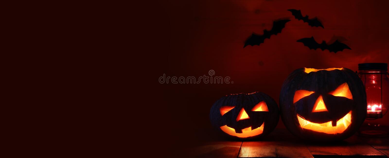 在木桌上的万圣夜南瓜在鬼的黑暗的背景前面 插孔灯笼o 库存照片
