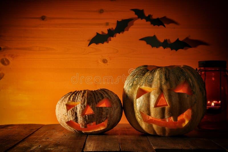 在木桌上的万圣夜南瓜在鬼的黑暗的背景前面 插孔灯笼o 图库摄影