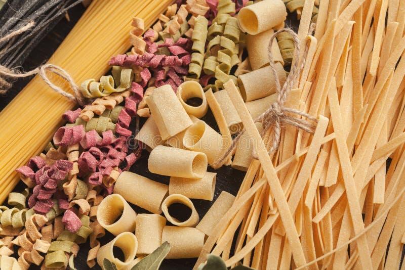 在木桌上的五颜六色的意大利面团和烹调成份 免版税图库摄影