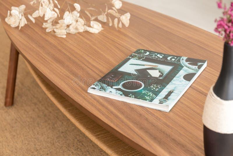 在木桌上的五颜六色的杂志在现代公寓时髦的客厅  免版税库存图片