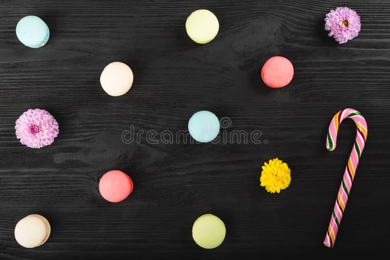 在木桌上的五颜六色的蛋白杏仁饼干 甜macarons、花和棒棒糖 与拷贝空间的顶视图您的文本的 免版税库存照片