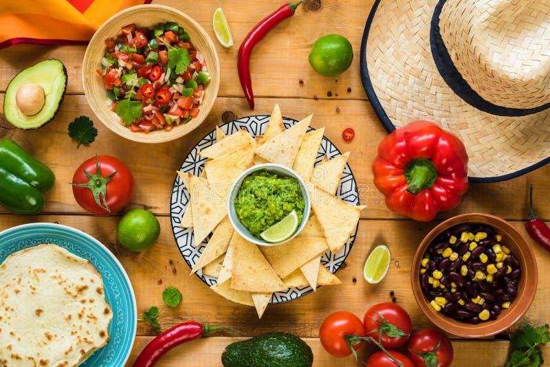 在木桌上的传统墨西哥食物 玉米片、鳄梨调味酱捣碎的鳄梨酱、烤干酪辣味玉米片、豆和辣调味汁 免版税库存图片
