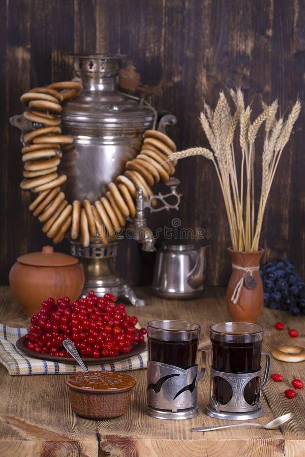 在木桌上的俄国传统水壶俄国式茶炊 红茶、百吉卷、红色荚莲属的植物、果酱和俄国俄国式茶炊在土气猪圈 免版税库存照片