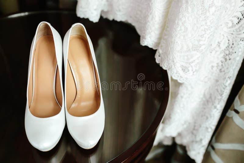 在木桌上的典雅的时髦的白色婚礼鞋子与一件礼服在背景中 库存图片