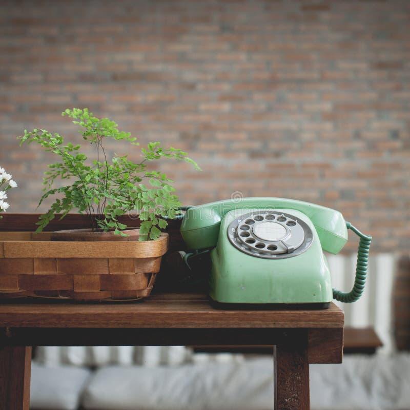 在木桌上的减速火箭的薄荷的绿色转台式电话 免版税库存图片