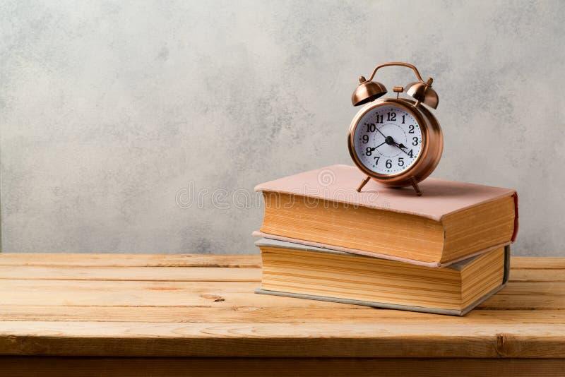 在木桌上的减速火箭的闹钟和葡萄酒书 免版税库存照片