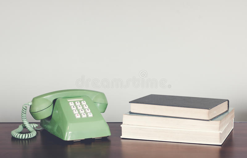 在木桌上的减速火箭的绿色电话与书葡萄酒口气 免版税库存照片