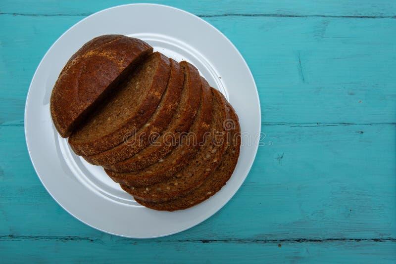 在木桌上的切的黑麦面包 库存照片