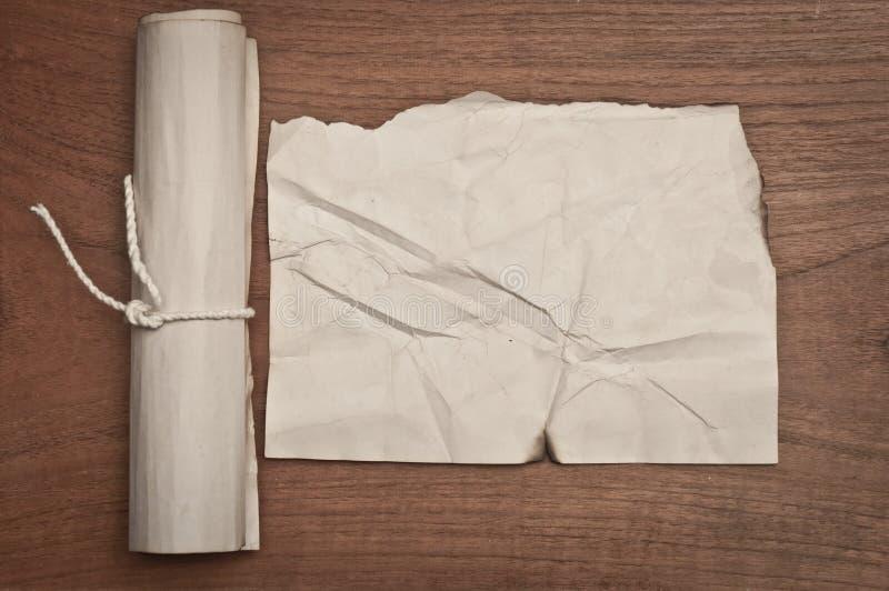 在木桌上的古老被弄皱的纸纸卷也许为背景使用 免版税库存图片