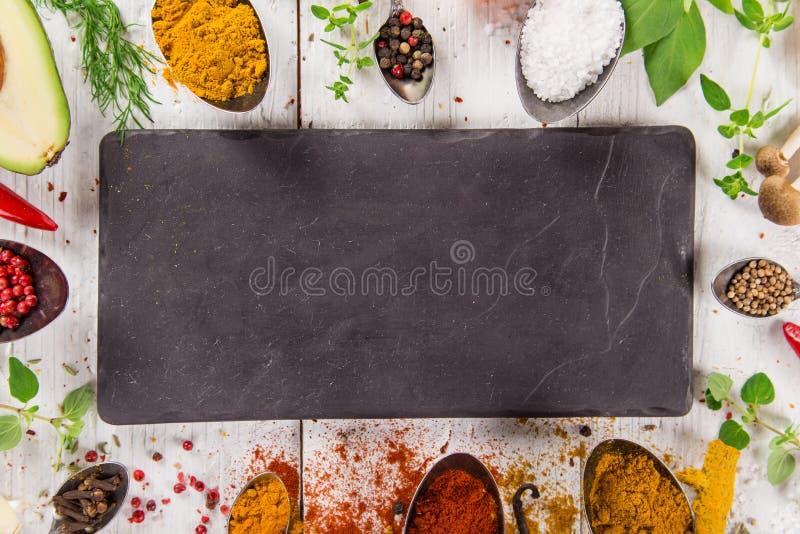 在木桌上的各种各样的五颜六色的香料 库存图片