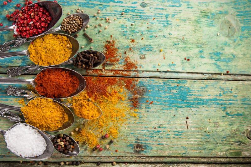 在木桌上的各种各样的五颜六色的香料 库存照片