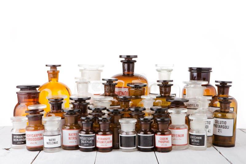 在木桌上的各种各样的葡萄酒药房瓶在药房 免版税库存图片