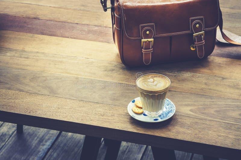 在木桌上的咖啡与皮包室外行家的生活方式 免版税库存图片