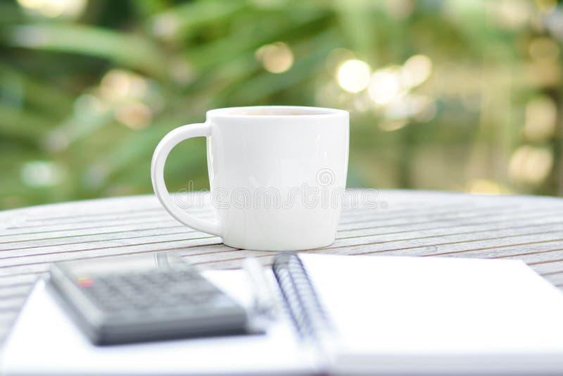 在木桌上的咖啡杯与计算器、笔和习字簿 免版税库存照片