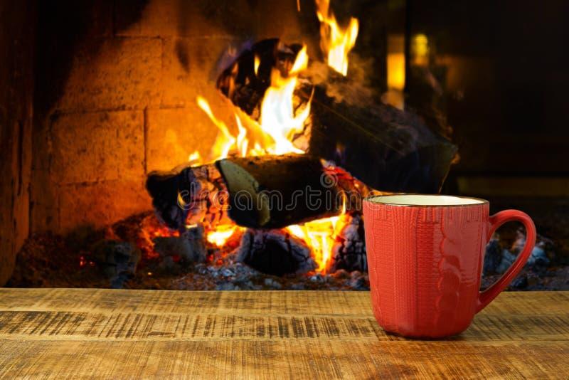 在木桌上的咖啡杯在壁炉 免版税库存照片