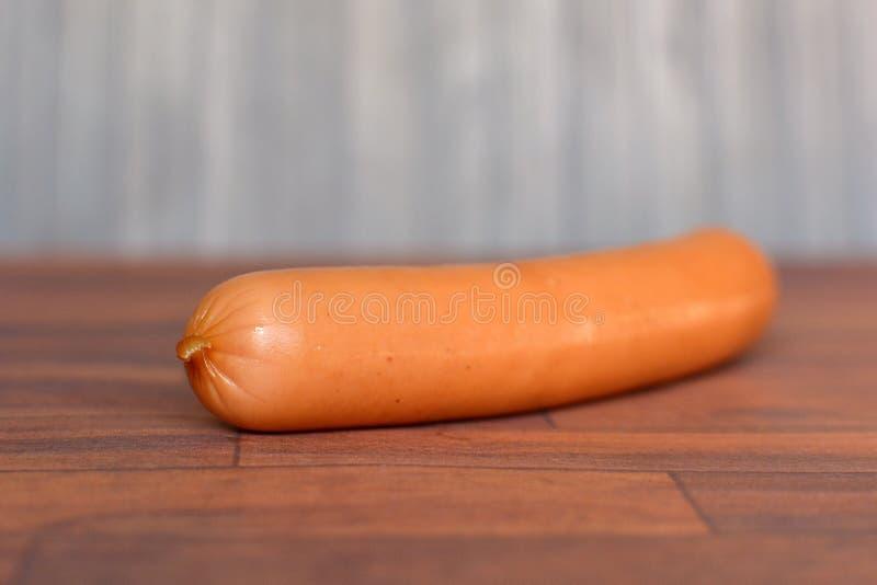 在木桌上的唯一维也纳香肠 免版税库存图片