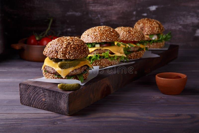 在木桌上的四个自创汉堡包 免版税图库摄影