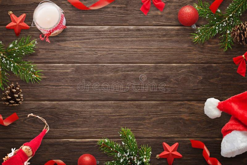在木桌上的圣诞节构成 冷杉分支、蜡烛、此外圣诞老人项目帽子、pinecones、玩偶、球和星 库存照片