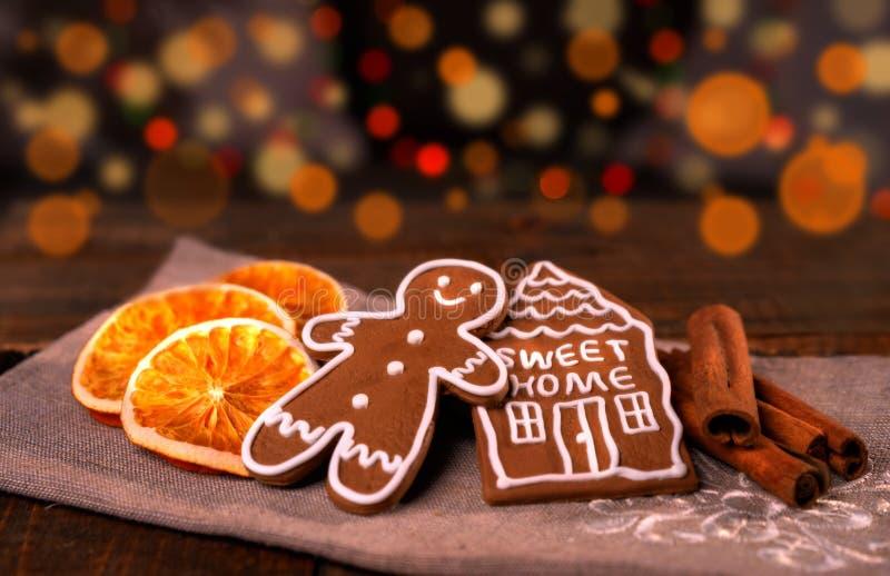 在木桌上的圣诞节自创姜饼曲奇饼,切片在背景的干燥橙色和色的光 免版税库存图片