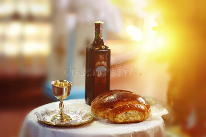 在木桌上的圣餐在教会里 圣餐采取 杯与红酒,在桌上的面包的玻璃 科珀斯克里斯提宴餐  库存照片