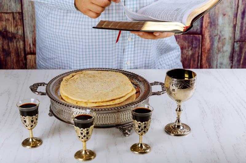 在木桌上的圣餐在教会 圣餐 杯玻璃用红葡萄酒、面包和圣经 免版税库存照片