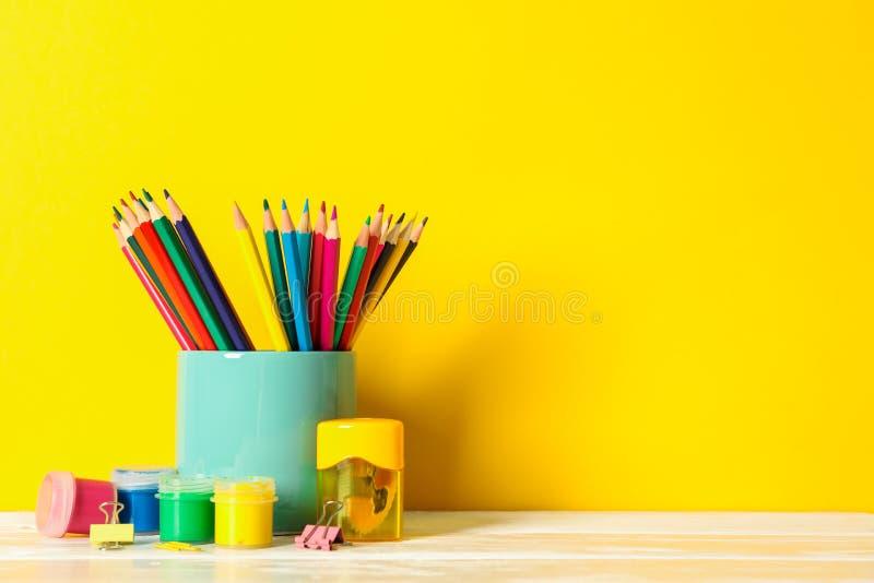 在木桌上的学校用品反对颜色背景 免版税库存图片