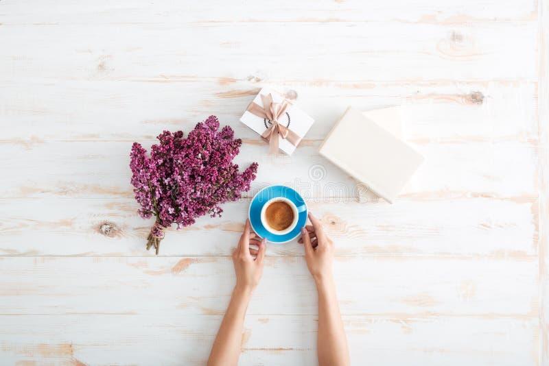 在木桌上的少妇饮用的咖啡的手 免版税库存照片