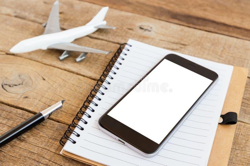 给在木桌上的屏幕和飞机模型打电话 免版税库存图片