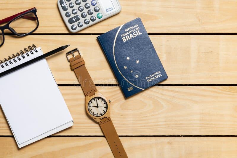 在木桌上的巴西旅行的护照和itens 库存照片
