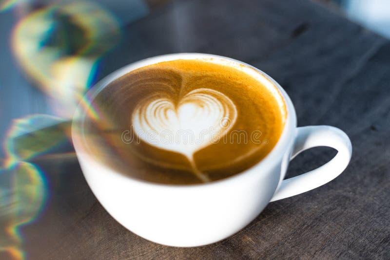 在木桌上的心形的咖啡拿铁 库存照片