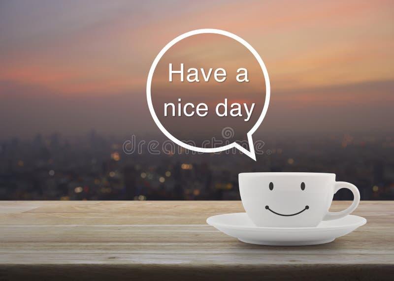 在木桌上的愉快的微笑加奶咖啡杯子在迷离都市风景 库存照片